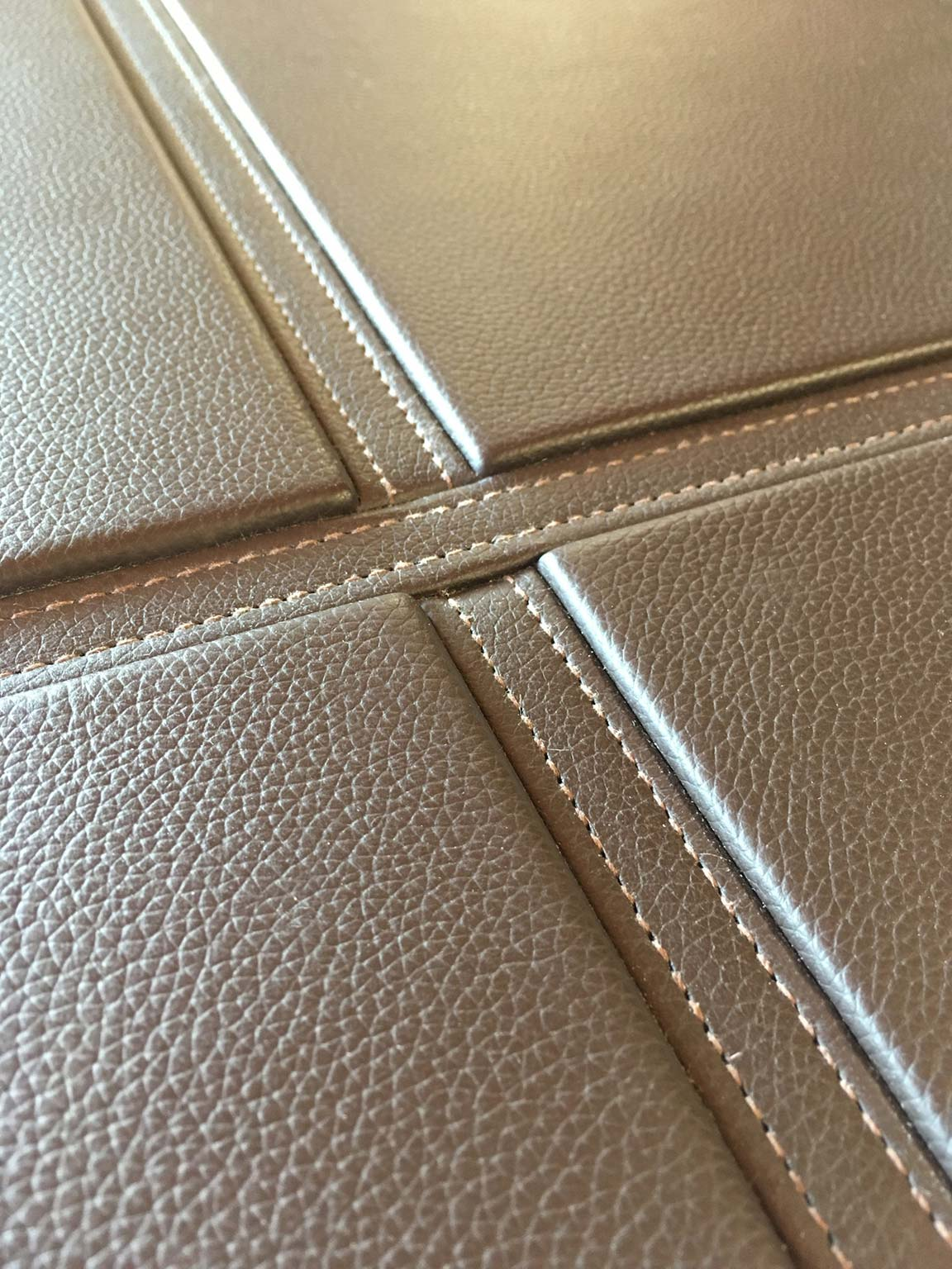 Leather wall panel detail of crossed strap design by Margan Ltd